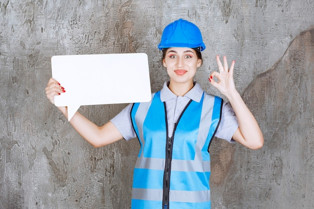 Female engineer in blue uniform and helmet holding a blank rectangle info board and showing enjoyment sign.