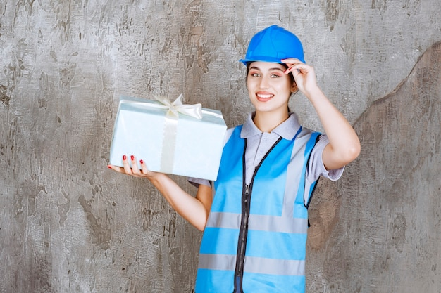 Female engineer in blue uniform and helmet holding a blue gift box.