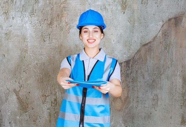 Female engineer in blue uniform and helmet holding a blue report folder and giving it for verification
