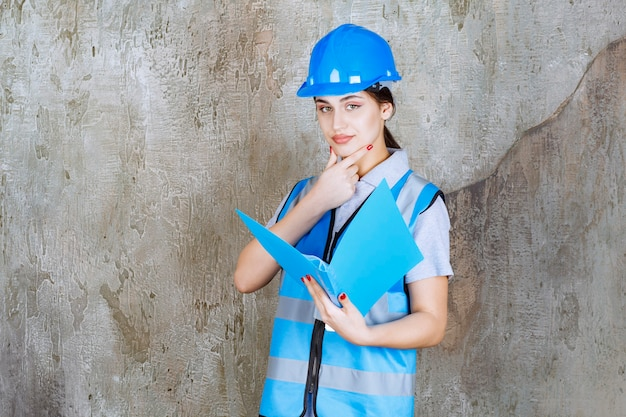 Female engineer in blue uniform and helmet holding a blue report folder and looks thoughtful.