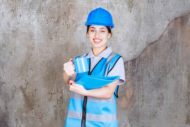 Female engineer in blue uniform and helmet holding a blue tea cup and a blue report folder and offering the drink to her colleague.