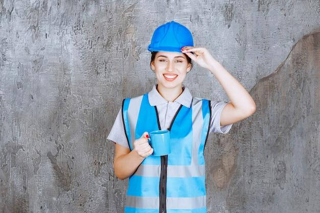 Ingegnere donna in uniforme blu e casco che tiene una tazza di tè blu