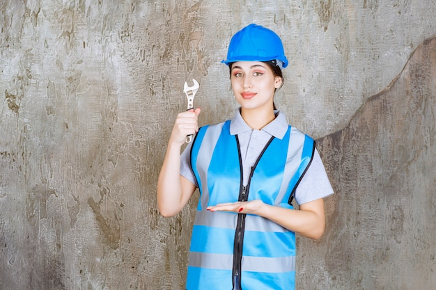 Ingegnere femminile in uniforme blu e casco che tiene una chiave metallica.