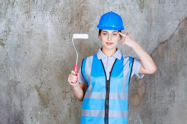 Ingegnere donna in uniforme blu e casco che tiene un rullo di assetto per dipingere, pensare e pianificare.