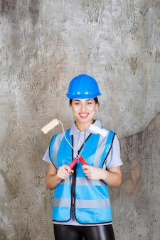Female engineer in blue uniform and helmet holding a trim roller for painting.