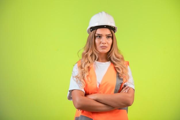 L'ingegnere femminile responsabile in casco bianco e attrezzi sembra depresso.