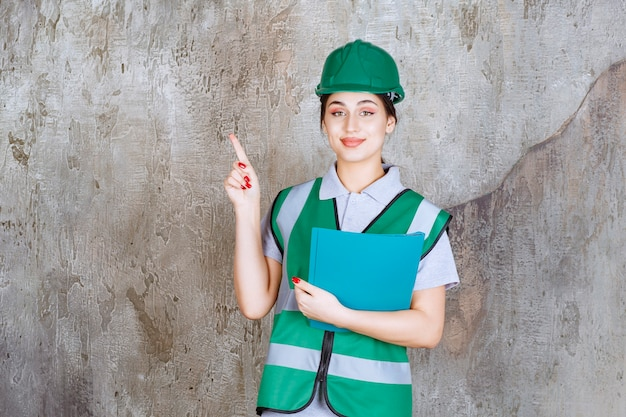 Ingegnere donna con casco verde che tiene una cartella blu e indica qualcuno intorno