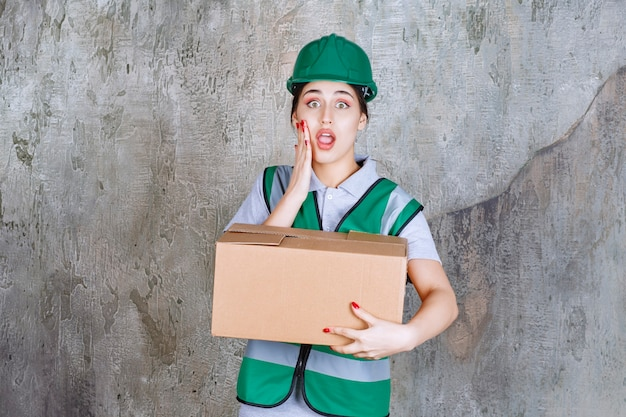Female engineer in green helmet holding a cardboard box and looks confused and terrified.
