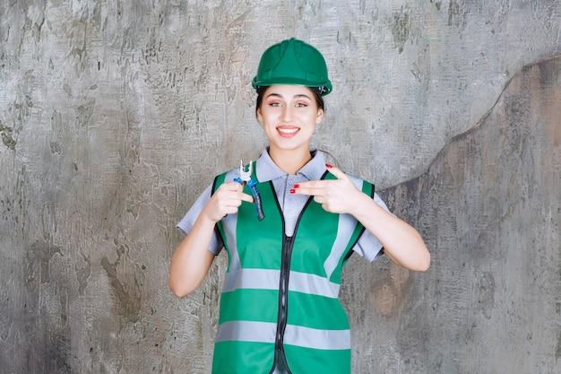 Ingegnere donna in casco verde che tiene le pinze per un lavoro di riparazione