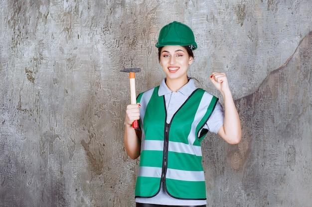 Ingegnere donna in casco verde che tiene un'ascia con manico in legno per un lavoro di riparazione e mostra i muscoli del braccio