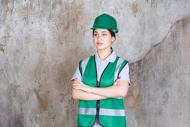 Female engineer in green uniform and helmet crossing arms and looks professional.