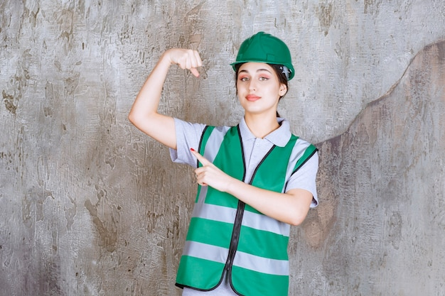 Female engineer in green uniform and helmet demonstrating her arm muscles.