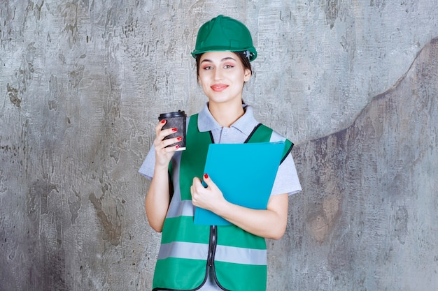 Female engineer in green uniform and helmet holding a black coffee cup and a blue project folder.