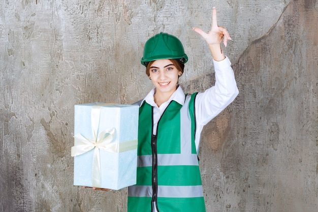 Female engineer in green uniform and helmet holding a blue gift box and having a good idea.