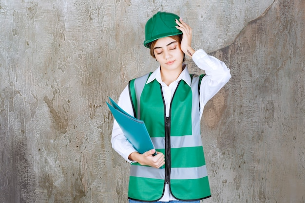 Female engineer in green uniform and helmet holding a green project folder and looks tired and sleepy