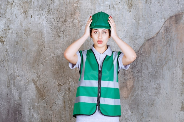 Female engineer in green uniform and helmet holding head and looks terrified