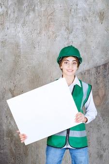 Ingegnere donna in uniforme verde e casco in possesso di un pannello informativo rettangolare