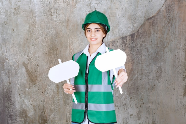 Female engineer in green uniform and helmet holding two sign boards in both hands.