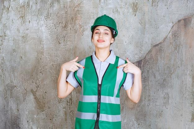 Ingegnere femminile in uniforme verde e casco che si presenta.