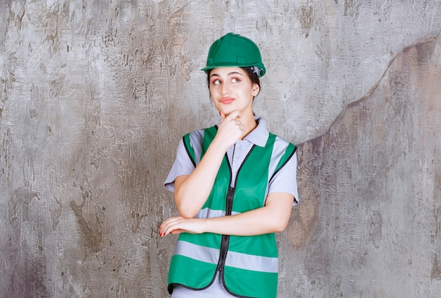 Female engineer in green uniform and helmet looks confused and thoughtful.