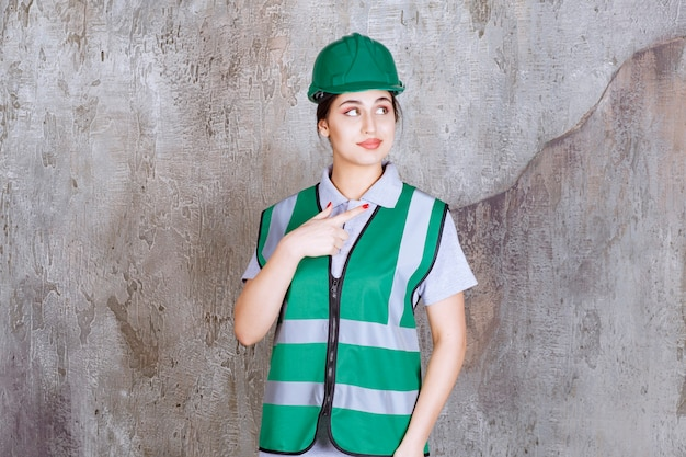 Female engineer in green uniform and helmet showing right side.