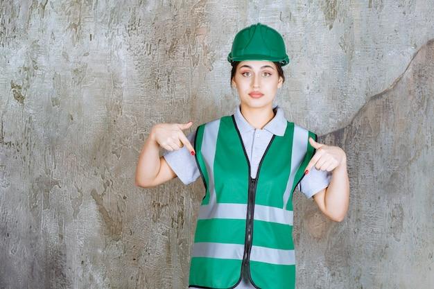 Ingegnere femminile in uniforme verde e casco che mostra qualcosa dietro.