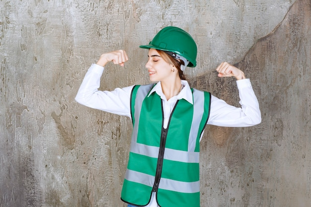 Female engineer in green uniform and helmet standing on concrete wall wall and demonstrating her arm muscles