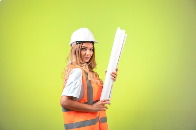 Female engineer in helmet and gear holding the construction plan and looks confident.