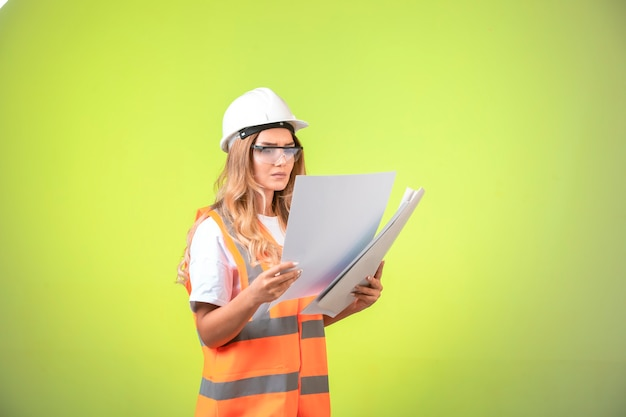 Female engineer in helmet and gear holding project plan and correcting it.