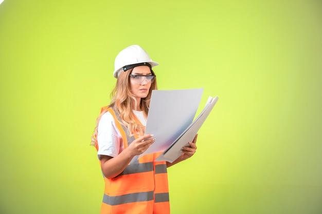 Ingegnere femminile in casco e attrezzi tenendo il piano di progetto e correggendolo.
