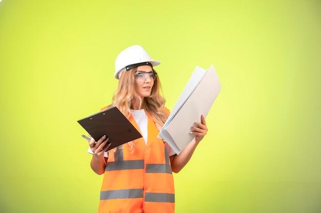 Ingegnere femminile in casco e ingranaggio che tiene il piano di progetto e l'elenco dei rapporti