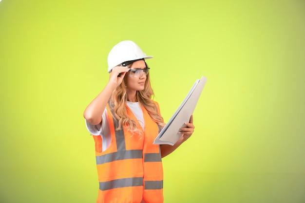 Ingegnere femminile in casco e attrezzi tenendo il piano di progetto e con gli occhiali.