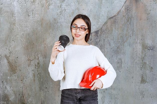 Женщина-инженер держит красный шлем и черную одноразовую чашку с напитком и выглядит задумчивой.