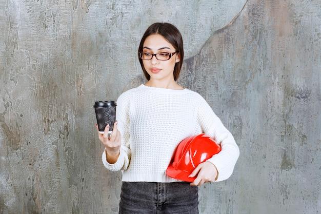 赤いヘルメットと黒い使い捨ての飲み物を持っている女性エンジニアは、思慮深く見えます。