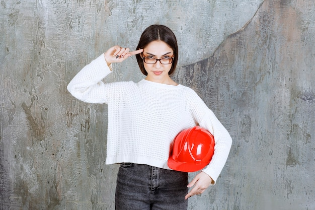 Женщина-инженер держит красный шлем и выглядит задумчивой или имеет хорошую идею.