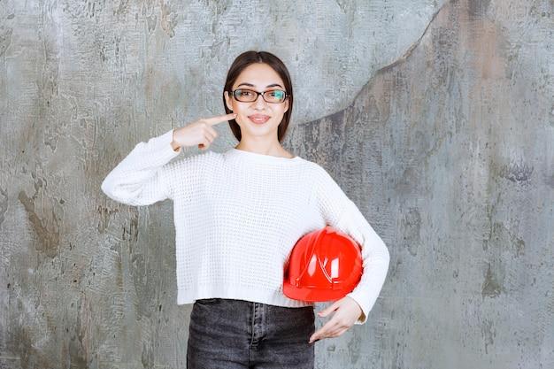 赤いヘルメットをかぶり、自分を指差す女性エンジニア。