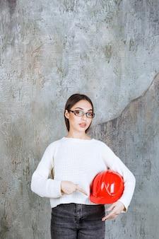 Женский инженер держит красный шлем и представляет его.