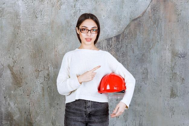 赤いヘルメットをかぶり、周りに何かを見せている女性エンジニア。