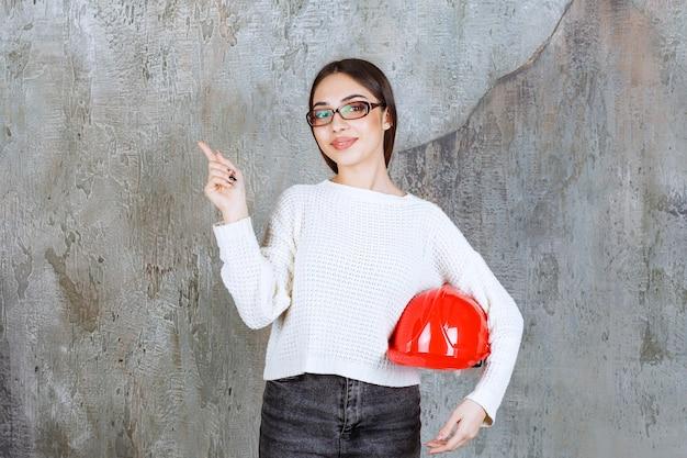 Женский инженер держит красный шлем и показывает что-то вокруг.