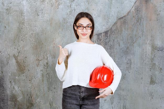Женский инженер держит красный шлем, показывая что-то позади.