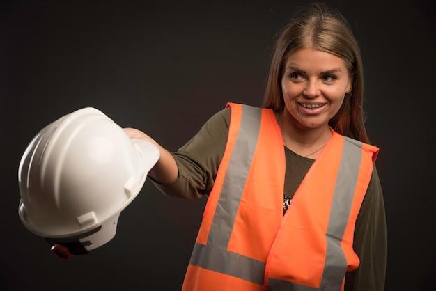 Женщина-инженер держит белый шлем и выглядит позитивно.