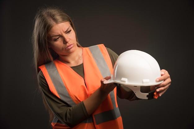 Женский инженер держит белый шлем и выглядит серьезно.