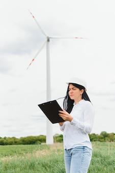 Женщина-инженер, держащая документы на ветряной электростанции