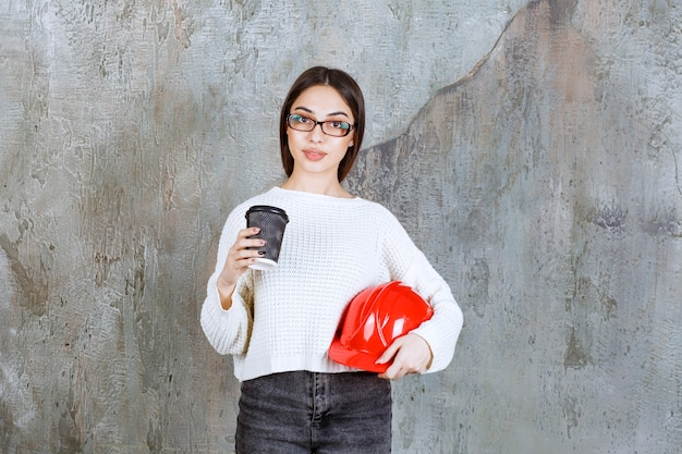 Female engineer holding a red helmet and a black disposable cup of drink.