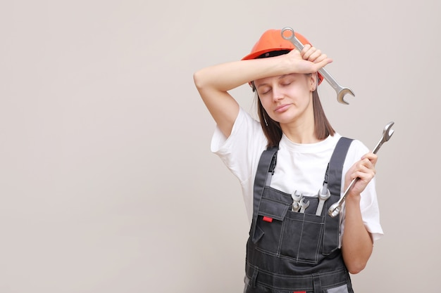회색 유니폼과 보호용 헬멧에 여성 엔지니어가 도구, 렌치로 그녀의 손에 미소 짓습니다.