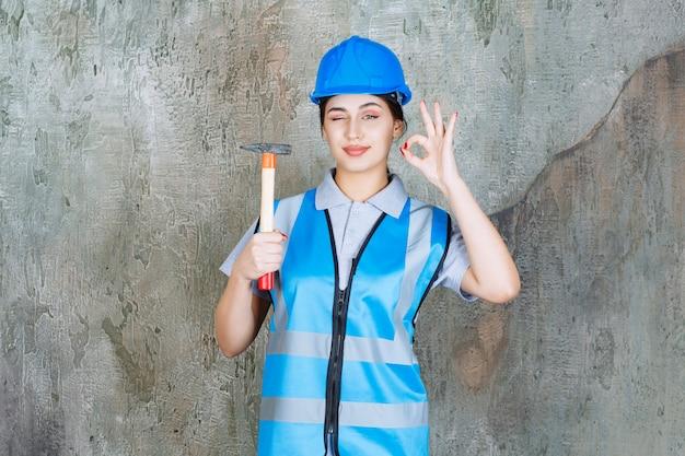 青いギアとヘルメットの女性エンジニアは、木製のハンドルと斧を保持し、肯定的な手のサインを示しています