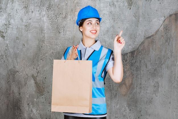 段ボールの買い物袋を持ってどこかを指している青いヘルメットとギアの女性エンジニア。