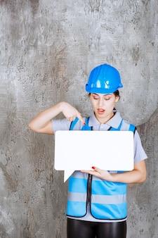 Женщина-инженер в синей форме и шлеме держит доску информации пустой прямоугольник и выглядит смущенной и напуганной.