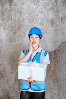 青い制服と青いギフトボックスを保持しているヘルメットの女性エンジニアは、驚いて興奮しているように見えます。