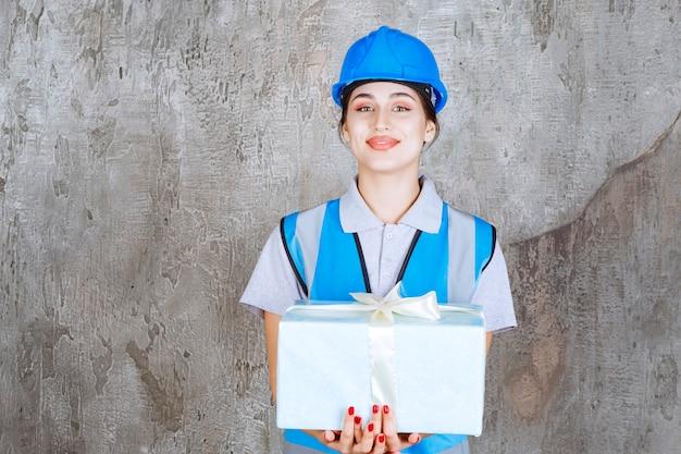 Женский инженер в синей форме и шлеме держит синюю подарочную коробку.